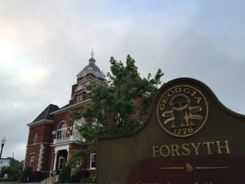 Angled shot of the Forsyth courthouse and city sign