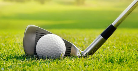 Golf Tourney event: Stock photo of golf club right behind golf ball on grass
